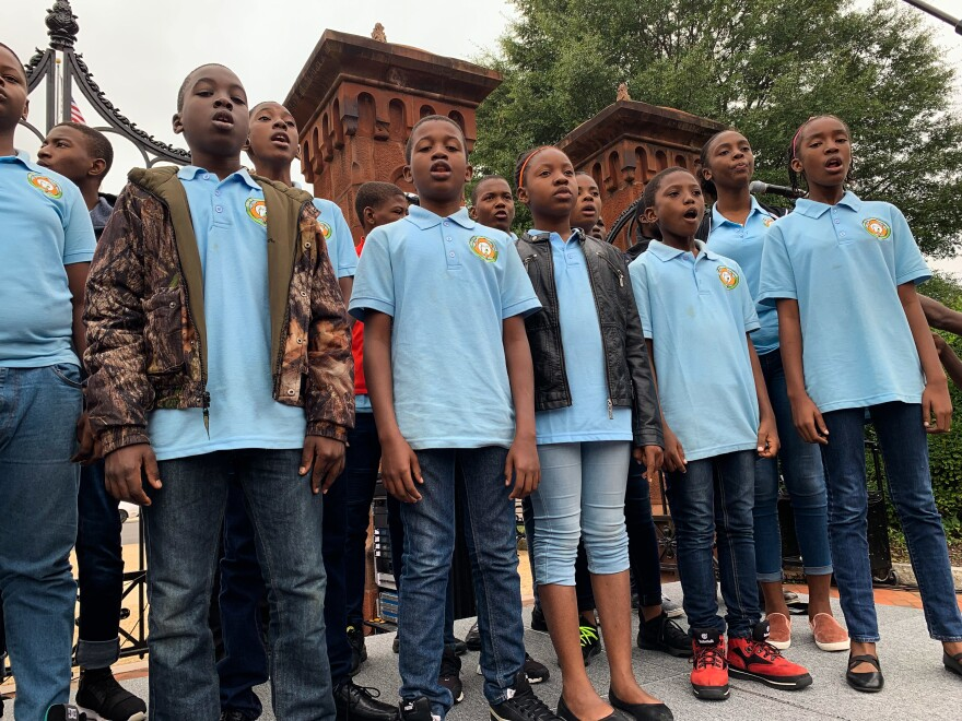 The youth choir from Haiti's Holy Trinity Music School warms up for their performance in the Smithsonian's Enid A. Haupt garden in Washington, D.C.