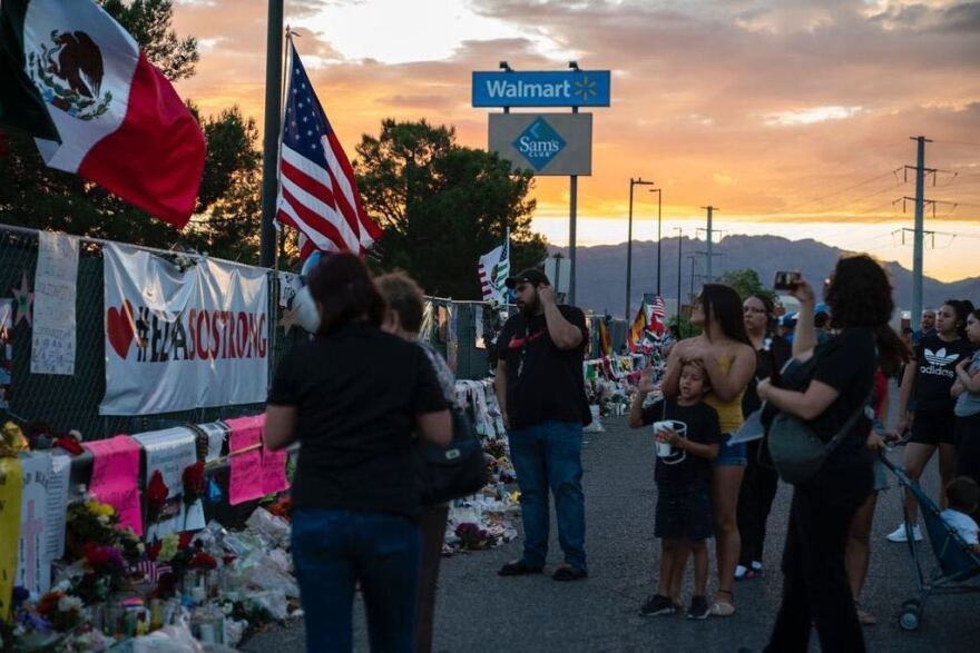 Community members visit a makeshift memorial outside a Walmart in El Paso, Texas, in the wake of a mass shooting at the store in August.