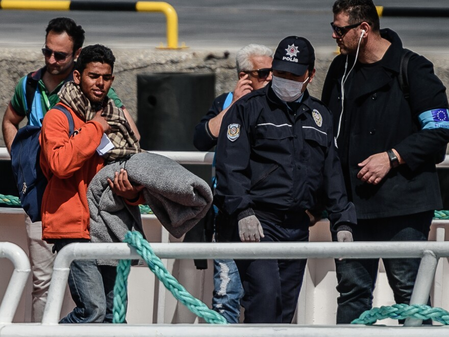 A police officer escorts a deported migrant from a small Turkish ferry carrying migrants deported from Greece as they arrive at the port of Dikili on Monday.