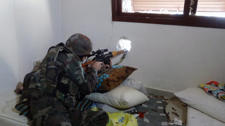 A Syrian soldier aims his rifle during clashes with rebel forces in the Damascus suburb of Daraya on Sunday. Syrian soldiers have been taking over private homes and apartments, and have sometimes looted and trashed them, according to Syrian civilians.