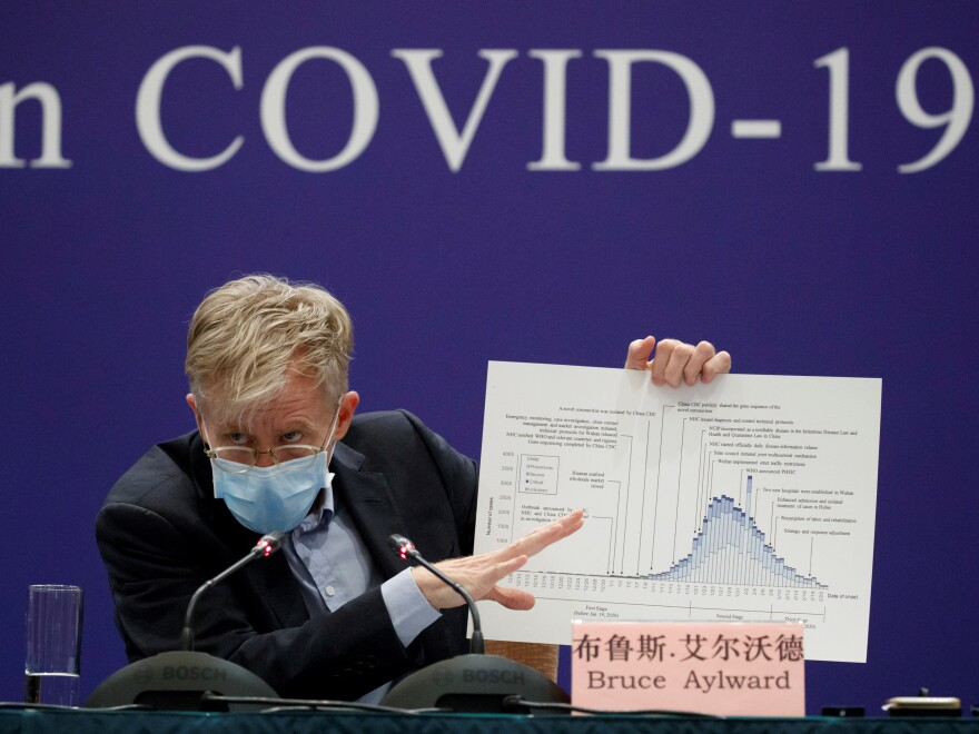 Bruce Aylward of the World Health Organization holds a chart about the COVID-19 outbreak during a briefing Monday in Beijing. The WHO says the virus has not risen to the level of a pandemic.