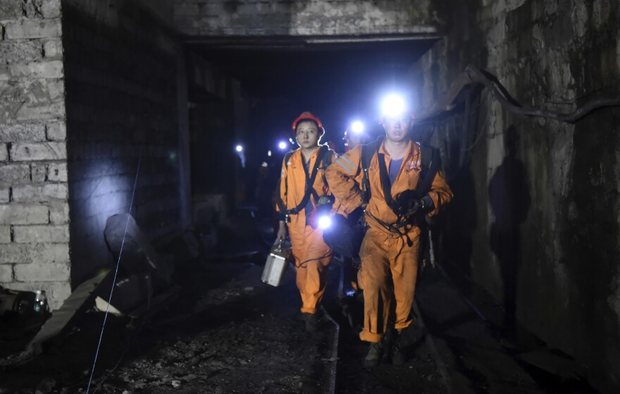 In a photo released by China's Xinhua News Agency, rescuers work at Jinshangou Coal Mine in Chongqing, southwest China, on Monday. An explosion at the mine has killed at least 13 people, and 20 more miners are either dead or trapped alive.