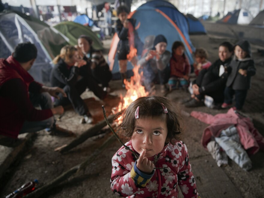 At the northern Greek border point of Idomeni on Friday, a migrant child eats as others sit around a fire in a railway-repairs hangar where people have set up their tents.