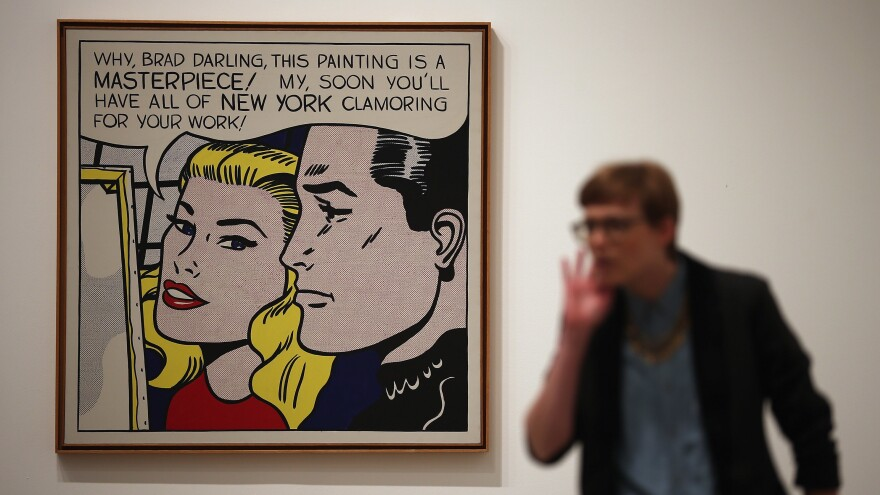 """A visitor stands in front of <em>Masterpiece</em> during a press preview of """"Lichtenstein, a Retrospective"""" at the Tate Modern in London in 2013. The iconic painting was owned by Agnes Gund, who recently sold it to fund a new criminal justice reform fund."""