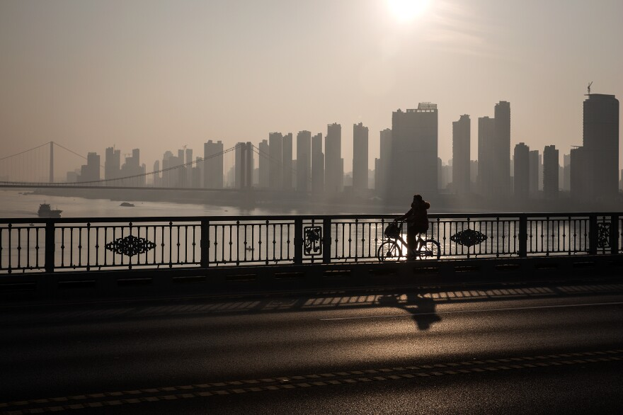 A cyclist crosses the Yangtze River Bridge. Residents of Wuhan are allowed to leave their homes on a limited basis. With public transit shuttered during the quarantine, they use cars, cabs, scooters and bicycles.