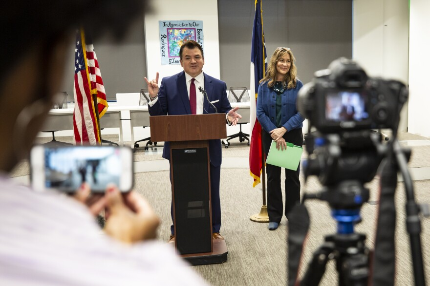 Outgoing AISD Superintendent Paul Cruz gives a Hook'em Horns salute as he speaks during a press conference about his resignation. Cruz is taking a position at UT Austin.
