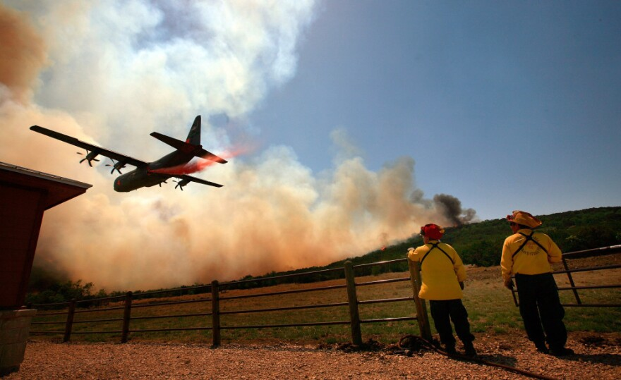 Emergency crews drop a fire retardant slurry on a running wildfire to save a house on April in Strawn, Texas, on Tuesday.