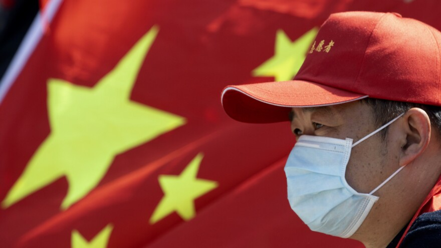 A volunteer looks out near a Chinese national flag during a farewell ceremony for the last group of medical workers who came from outside Wuhan to help the city during the coronavirus outbreak in Wuhan in central China's Hubei province on Wednesday.