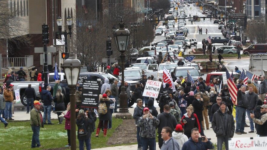 Flag-waving, honking protesters drove past the Michigan Capitol on Wednesday to show their displeasure with Gov. Gretchen Whitmer's orders to keep people at home and businesses locked during the COVID-19 outbreak.