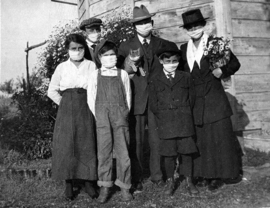 A mother and father stand with their three sons, daughter and cat in front of a rural house during the 1920 flu epidemic.