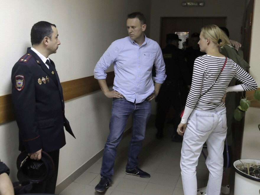 Russian opposition leader Alexei Navalny, center, and his wife Yulia talk before a hearing in a Moscow court on Monday. Navalny was arrested Monday morning.