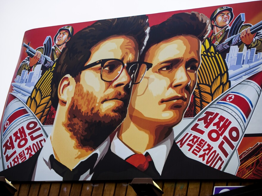 A banner for <em>The Interview</em> is posted outside Arclight Cinemas, in the Hollywood section of Los Angeles on Wednesday. The theatrical release of the film has been cancelled following cyber attacks and threats believed to originate in North Korea.