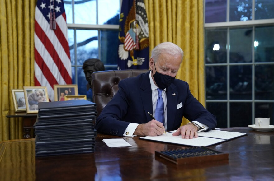 President Biden signs his first executive action in the Oval Office Wednesday afternoon.