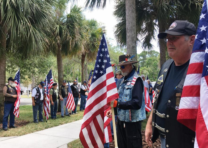 veteran_riders_line_the_sidewalk_holding_american_flags_for_the_duration_of_the_service.jpg