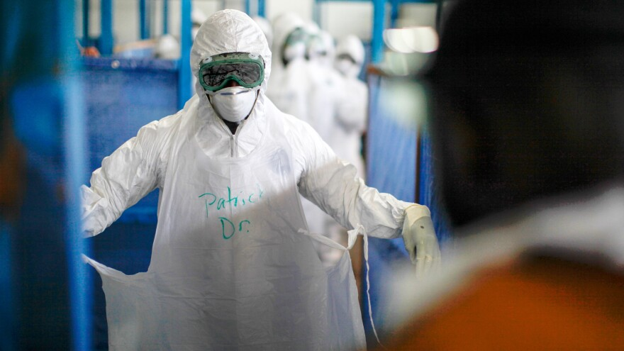 Dr. Patrick Lahai Kamara of Liberia wears the standard World Health Organization protective gear. Some exposed skin is allowed. The material for the suit and gloves is not as thick as the Doctors Without Borders equipment.