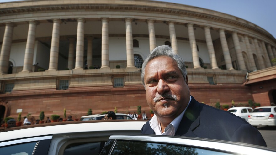 Indian business tycoon Vijay Mallya, the owner of Kingfisher Airlines, gets into his car outside Parliament in New Delhi, India, in 2013. Mallya, who owes large sums on loans to his businesses, recently left the country for Britain, according to reports.