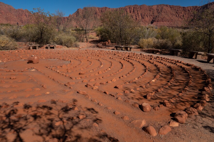 Rocks are laid out in a labyrinth formation against a backdrop of red rock cliffs.
