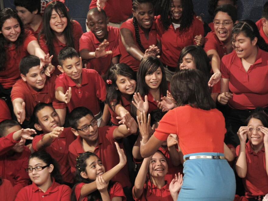 First lady Michelle Obama has been doing a lot of high-fiving with schoolchildren like these in Dallas to promote healthful lifestyles. Now she's diving more deeply into the politics of school lunch.