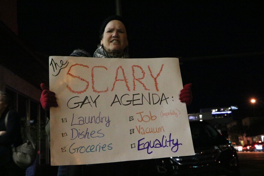 """Woman in beanie holds sign that reads, """"the scary gay agenda"""" below is a checklist of items, """"laundry, dishes, groceries, job, vacuum, equality."""""""