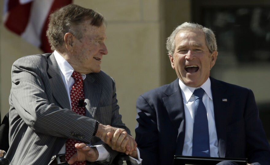 George H.W. Bush (left) congratulates his son George W. Bush as the two former presidents attend last year's dedication of the George W. Bush Presidential Center in Dallas.