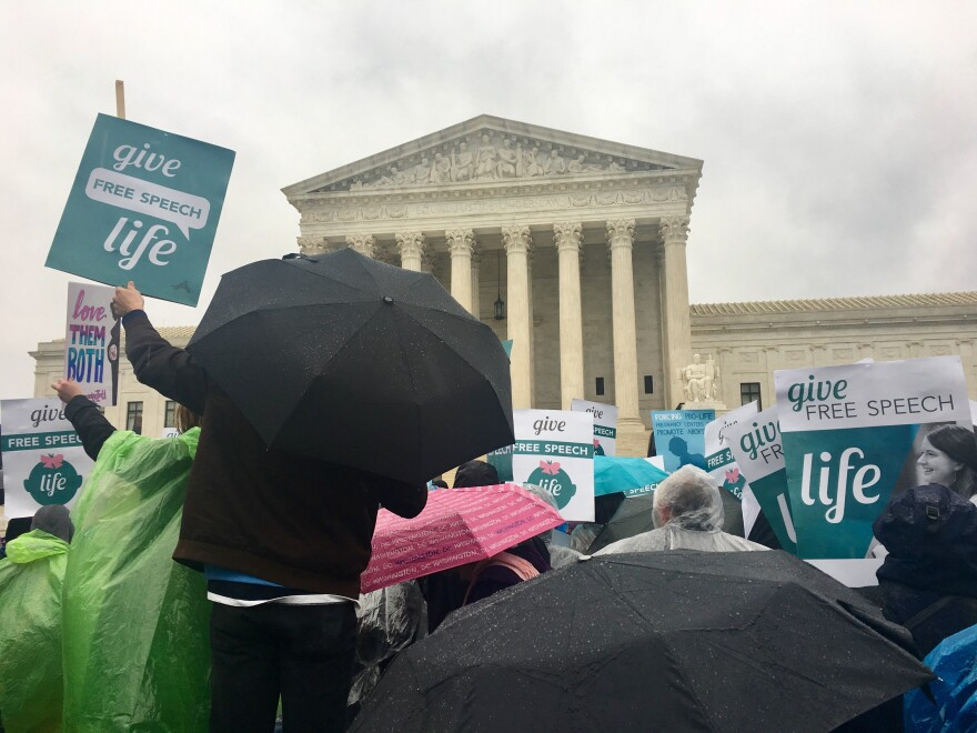 Anti-abortion activists protest in the rain in front of the Supreme Court. The court is hearing arguments Tuesday on the state of crisis pregnancy centers.