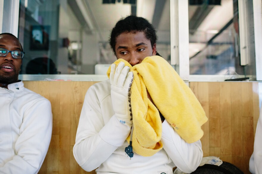 Jason Pryor (center) and his friend and fellow fencer Dwight Smith (left) take a break during training at the Fencer's Club in New York City on June 17.