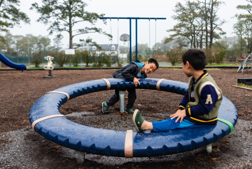 Henry pushes a wheel as Hayle sits on it in a park in Chincoteague, Md., on April 14, 2019.