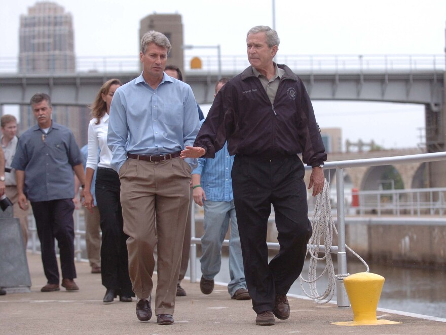 Minneapolis Mayor R.T. Rybak and President George W. Bush tour an area near a collapsed interstate bridge, which left 13 people dead in 2007.