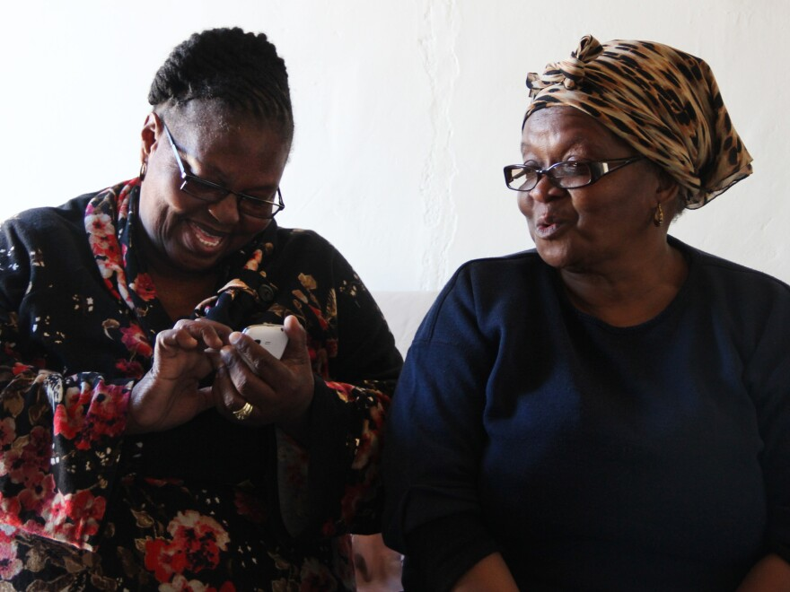 Gloria Gxebeka (left) visits Leona Mqhayi and types her health information into a cell phone