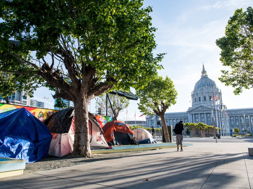 Tents line a gravel sidewalk off Fulton Street near City Hall in San Francisco on May 5. Last week, city staffers started using chalk to draw socially distant spaces along the street for the tents to stay in.