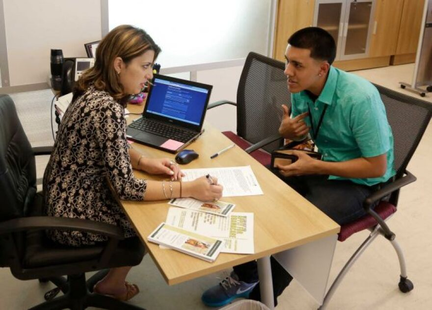 In this Nov. 17, 2014 file photo, navigator Dianelys Dominguez, left, assists Giovanny Vega, 18, of Miami, right, sign up for health insurance under the Affordable Care Act at the Borinquen Medical Center in Miami.
