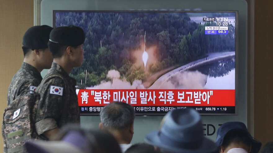 South Korean soldiers in Seoul walk by a TV news program showing a file image of a missile being test-launched. North Korea on Tuesday test-launched another ballistic missile in the direction of Japan, U.S. and South Korean officials said.