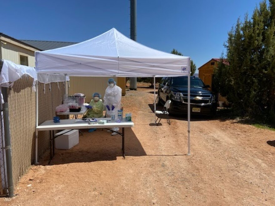Photo showing two people wearing personal protective equipment are under a tent outside