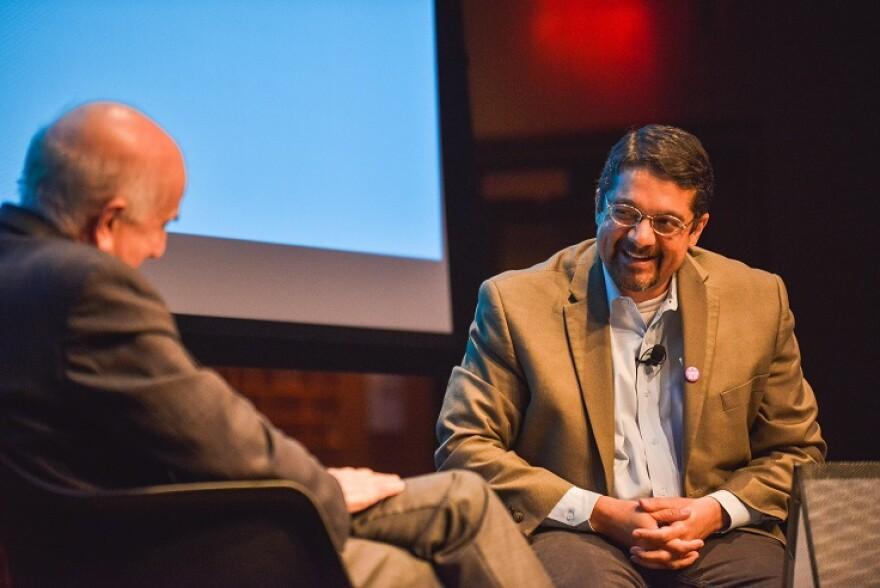 NPR's Shankar Vedantam sits on a stage laughing with another man in an interview setting.