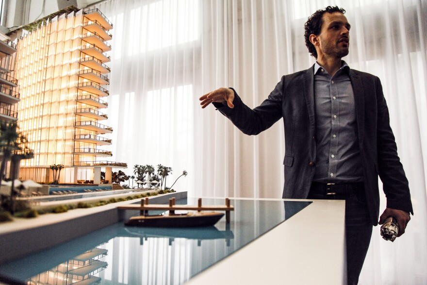 Simon Koster of JDS Development Group points to a model of the Monad Terrace luxury development, which is being built with climate change in mind.