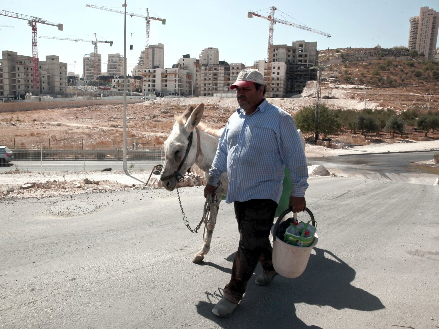 A Palestinian man walks near a construction site of a new housing unit in a neighborhood in East Jerusalem known to Jewish settlers as Har Homa and to Palestinians as Jabal Abu Ghneim. The Palestinians want East Jerusalem to be the capital of a future state and object to Israeli building there and throughout the West Bank. Israel claims all of Jerusalem as its capital.