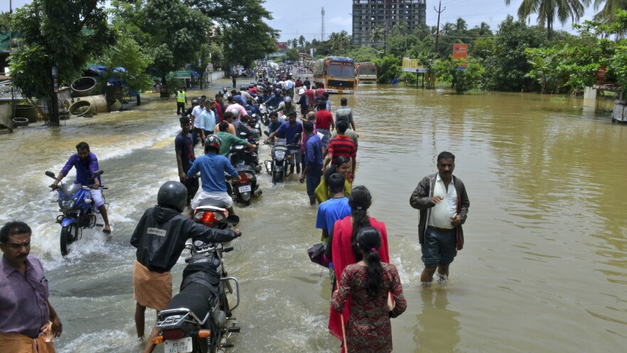 People move past a flooded road in the southern Indian state of Kerala, where monsoon rains have destroyed roads and left hundreds of thousands of people homeless.