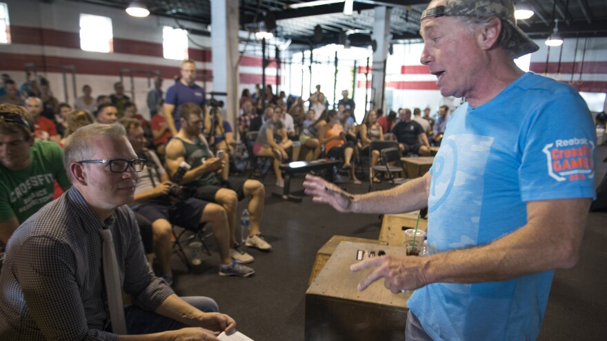 CrossFit founder and CEO Greg Glassman (right) talks to employees in Washington, D.C., in 2015. In recent days, Glassman and his company had come under fire over his comments about the Black Lives Matter movement.