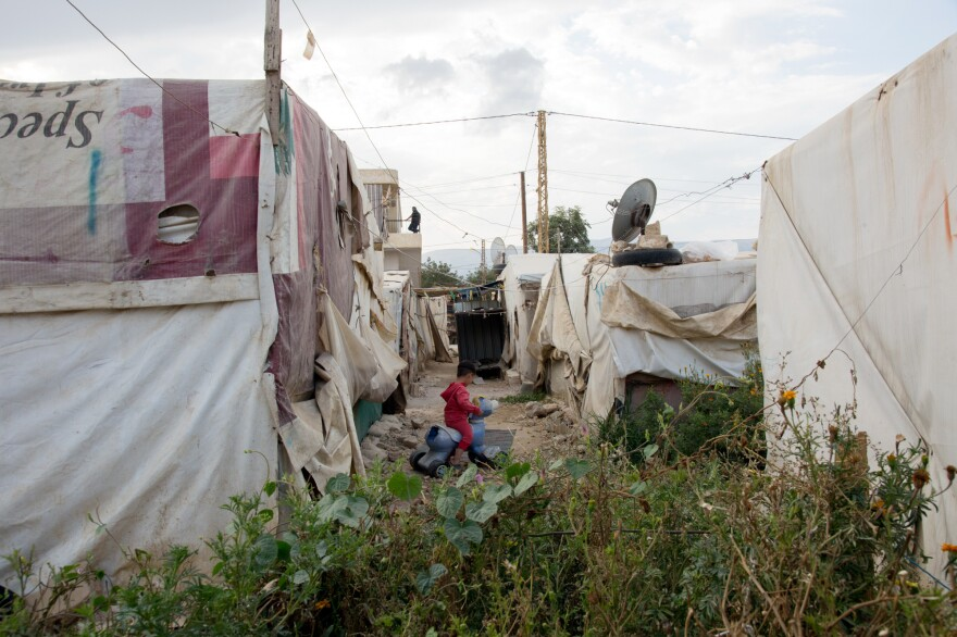 A Syrian child plays outside his tent in the informal refugee settlement where Fatmeh lives with her family in eastern Lebanon's Beqaa Valley.
