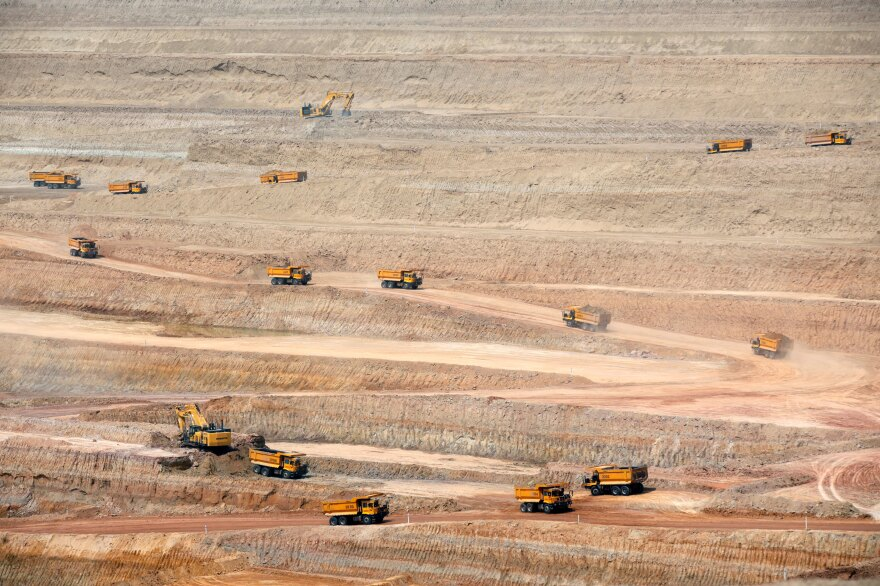 Dump trucks drive at the open-pit coal mining site in Islamkot, in the Thar desert in Pakistan in 2017.
