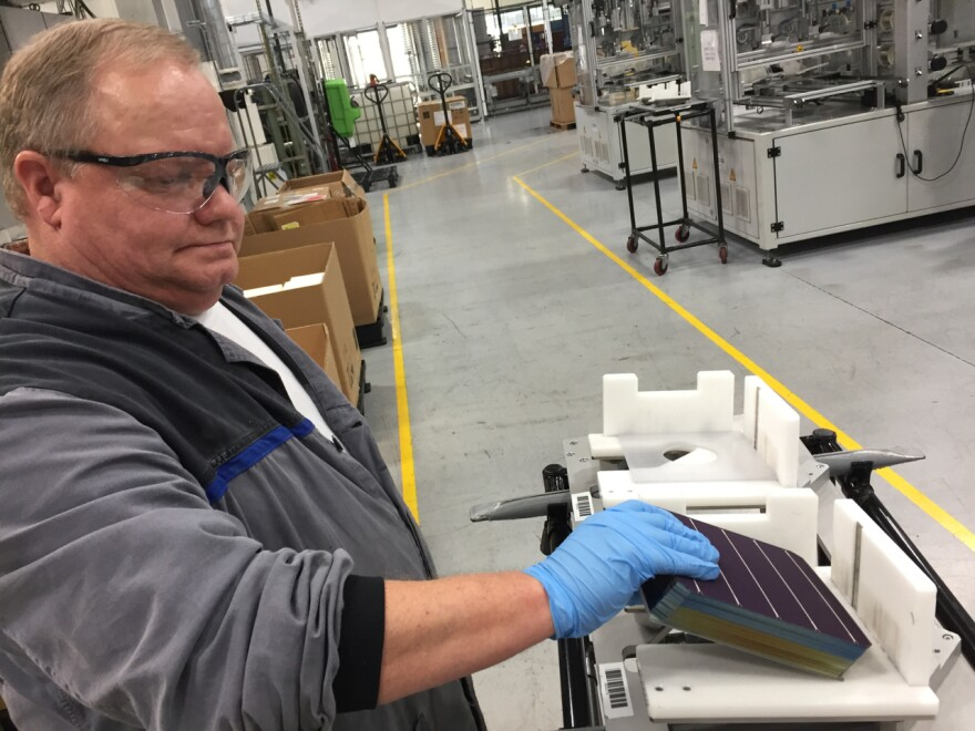 At the SolarWorld manufacturing plant in Hillsboro, Ore., John Clason stacks solar cells before loading them into machines that build solar panels.