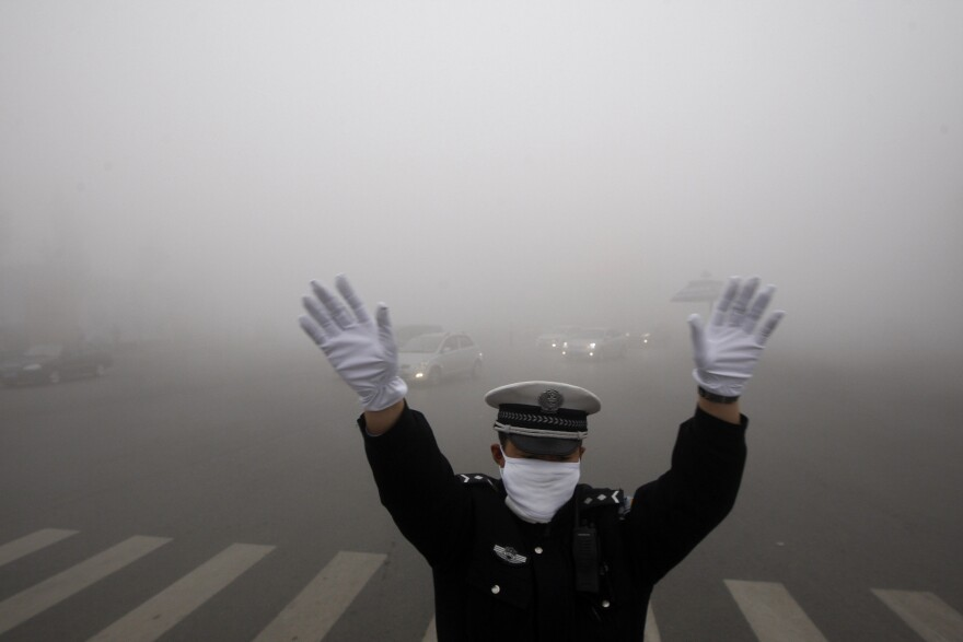 A policeman gestures as he works on a street in heavy smog in Harbin, northeast China's Heilongjiang province, on Monday.