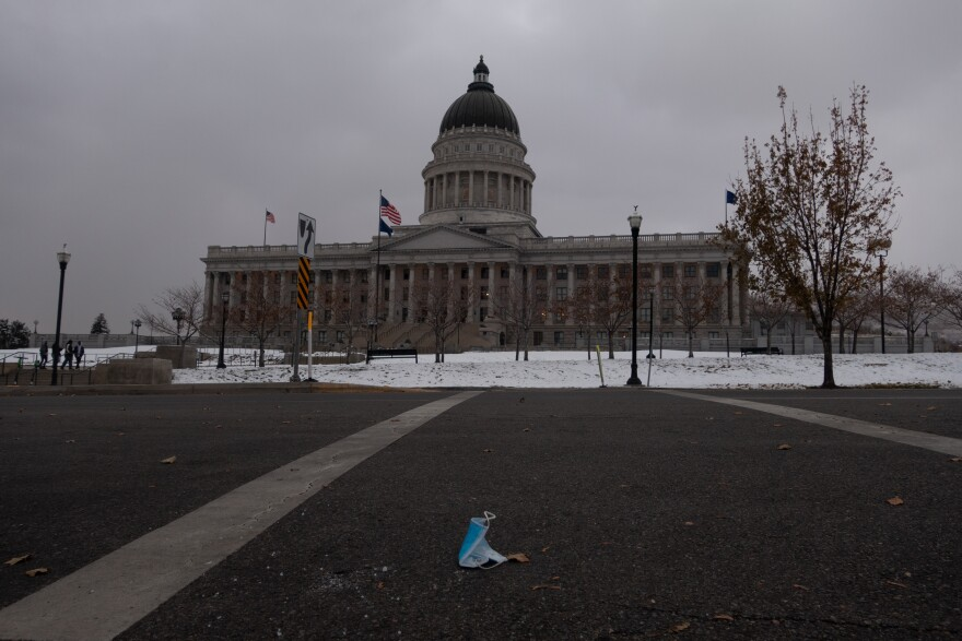 A photo of a face mask on the ground in front of the Utah State Capitol.