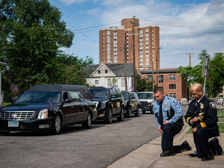 Minneapolis Police Chief Medaria Arradondo (right) kneels as the hearse of George Floyd arrives to North Central University ahead of funeral service on Thursday. Protests in the wake of Floyd's death while in police custody has erupted across the country.