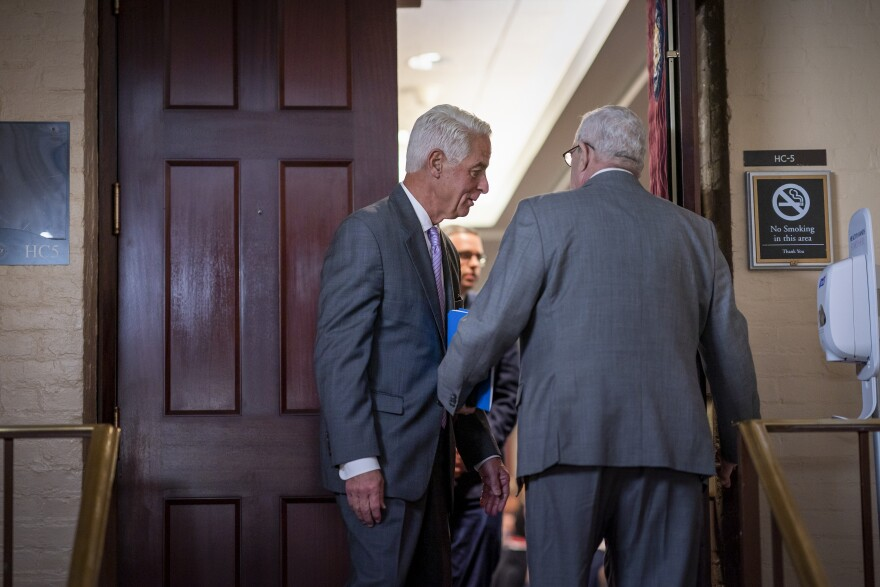 Rep. Charlie Crist, D-Fla., center, pauses to speak with Rep. Gerry Connolly, D-Va., right, in the doorway to a closed House Democratic caucus meeting called by Speaker of the House Nancy Pelosi, D-Calif., as she moves  toward House passage of a coronavirus aid package possibly this week, on Capitol Hill in Washington, Wednesday, March 11, 2020. (AP Photo/J. Scott Applewhite)
