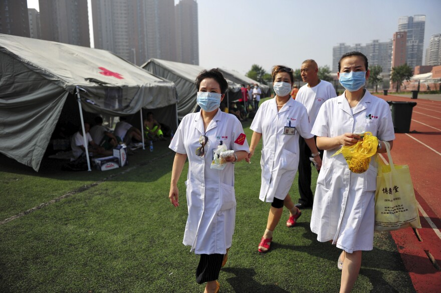 Medical volunteers walk past tents set up on the playground of a primary school as temporary shelters for victims after explosions in Tianjin, China, on Aug. 13.