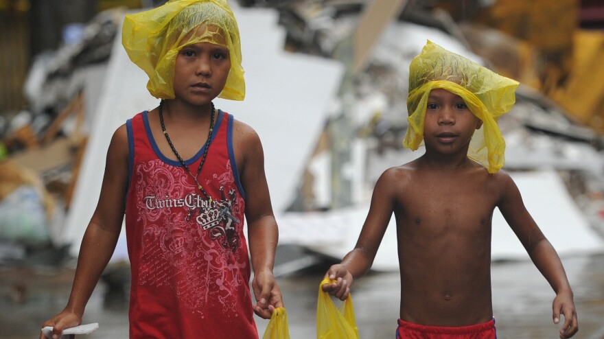 Young survivors of Typhoon Haiyan brave December rain as they ask for gifts from residents in the streets of Tacloban, the Philippines. Months after the storm, cleanup is still ongoing and many of the more than 6,000 dead have yet to be identified.