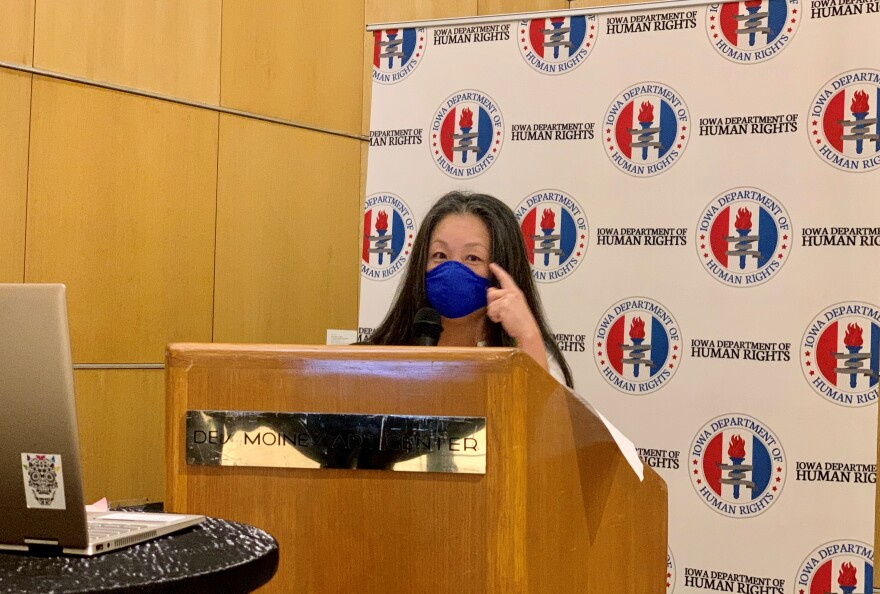 A woman stands behind a podium wearing a blue face mask and points to her eyes.