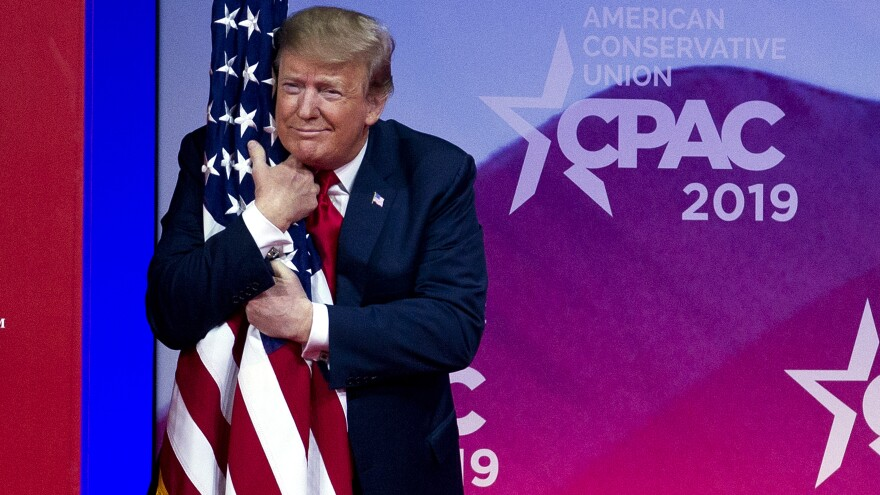 President Donald Trump hugs the American flag before his speech at the Conservative Political Action Conference.