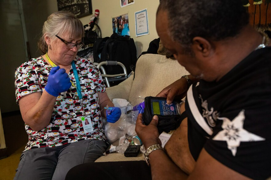Arthur Jackson (right) gets blood tests during home visits in Boston from nurse Brenda Mastricola. He's also getting intravenous penicillin to treat a serious bone infection in his foot. The medication's pump is connected to an indwelling IV catheter. It's still uncommon for patients with a history of injection drug use to be sent home with an IV.